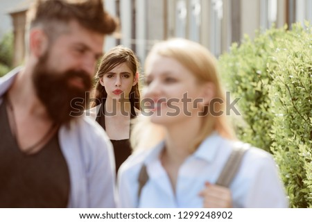 Terribly jealous of them. Romantic couple of man and woman dating. Bearded man cheating his girlfriend with another woman. Jealous woman look at couple in love on street. Unhappy girl feeling jealous. Stockfoto ©