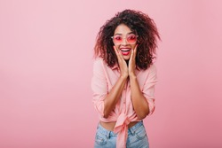 Terrific african model expressing surprised emotions while posing on indoor photoshoot. Stylish curly woman in sunglasses having fun in pink studio.