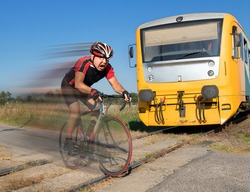 Terrified cyclist is rushing before by train on the tracks. Shocked biker ride a railway crossing in front of an approaching train. The regional train coming to road with hurry bicyclist on crossing.