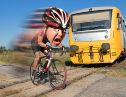 Terrified cyclist is rushing before by train on the tracks. Shocked biker ride a railway crossing in front of an approaching train. The regional train coming to a road with a hurry bicyclist..
