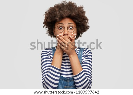 Terrified dark skinned cute young female with Afro hairstyle, covers mouth with great fear, tries not to cry, has scared shocked expression, wears striped sweater, isolated over white background. #1109597642