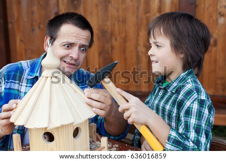 Terrified man holding nail while son handles the hammer - parenting mishaps #636016859