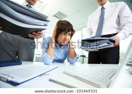 Terrified secretary touching her head while looking at big heaps of papers