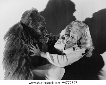 Terrified woman being attacked by gorilla - stock photo