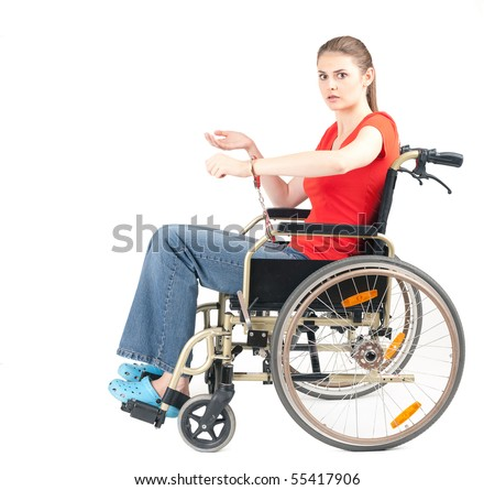 stock photo : terrified woman pinned to wheelchair by handcuffs