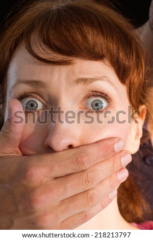Terrified woman with covered mouth on black background