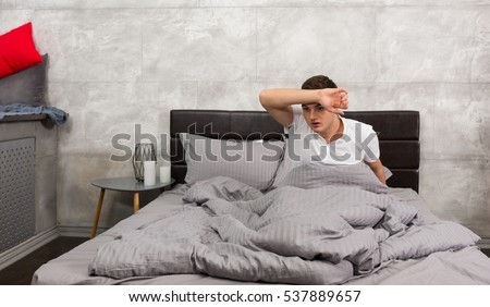Terrified young man woke up from a nightmare and wiping sweat from his forehead while sitting in stylish bed with grey colors in a bedroom in loft style #537889657