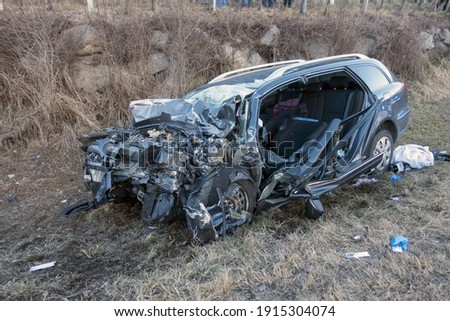 Terrifying deadly car crash accident after a frontal collision. Twisted metal and destruction after a violent head-on collision between two cars on the road. Foto stock ©