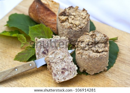 Terrine of pork on a wooden board in a kitchen