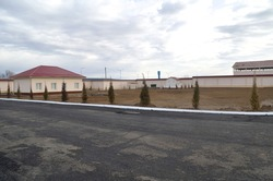 Territory is in an industrial zone fenced with a large plot of land and a one story building