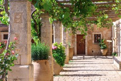 Territory of the old monastery. Courtyard of the monastery with a blooming garden. Arkadi, Crete, Greece