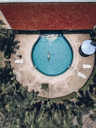 Territory of the tropical hotel,  beautiful woman floats on the back in the round blue pool, flecks in the blue water. Terracota roof tile, palmtrees, aerial view