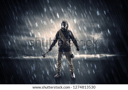Terrorist in a stormy space with gas mask on his hand and weapons on his arm #1274813530