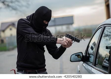 Terrorist or a car thief pointing a gun at the driver - car owner