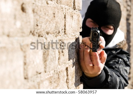 Terrorist robber pointing with black pistol gun.Portrait of suspect, terrorism attack.Place for text on left.Portrait of man in black mask aiming with 9mm pistol.Armed and dangerous suspect.Careful