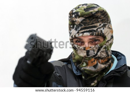 terrorist with mask aiming with his gun over white