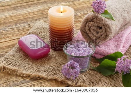 Terry towels, soap for bathroom procedures, sea salt, burning candle and lilac flowers on sackcloth and old wooden boards. Spa products and accessories.