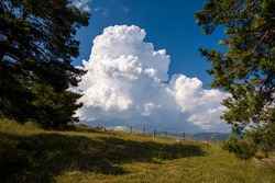 Teruel Spain blue sky with cumulus cloud forming over the mountains.