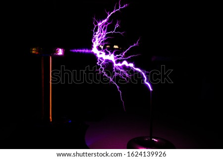 Tesla coil in operation with lightning strikes