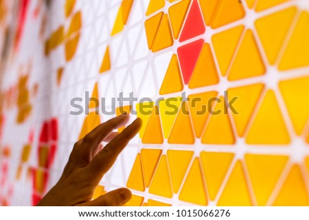 tessellation of a plane with yellow, orange and red colored triangles on a white background. mathematical and artistic game to cover a surface with geometric shapes. kids play math games with hand #1015066276