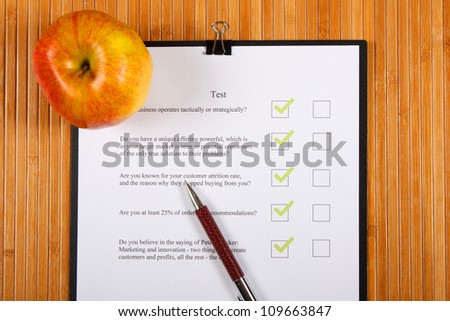 Test and an apple on a wooden table