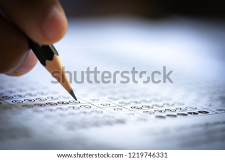 Test exam concept, pencil writing answer on paper answer of question in examination test. It assessment intended to measure knowledge, skill, aptitude, physical fitness, or classification students