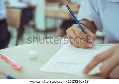 test exam for education in school concept : University student holding pencil notes paper on answer sheet at lecture chair for taking exams in examination classroom. Assessment learning in class ideas #1523260919