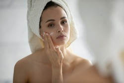 Test for allergy. Careful young woman with sensitive skin applying small spot of hypoallergenic delicate cream lotion serum of natural organic ingredients on her chick after shower to look at result