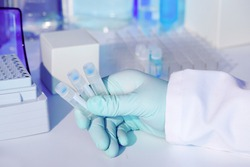 Test kit to detect presence of RNA virus in patient samples. RT-PCR kit reagents convert viral RNA to DNA and amplify unique region specific for virus. Hand in glove holding test tubes.