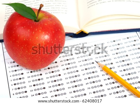 Test score sheet with answers, book and apples