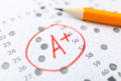 Test score sheet with answers, grade A+ and pencil, close up