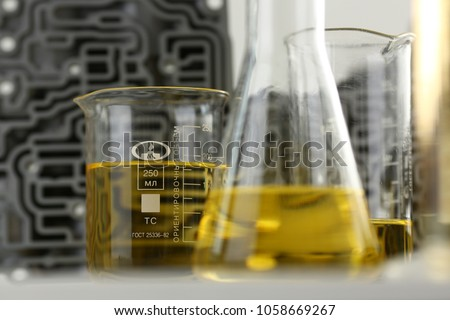 Test tube chemistry flask against background of hydroblock acp with yellow liquid purified oil from recycling and lubricating materials sale closeup