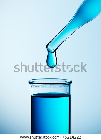 Test tube with pipet over blue background