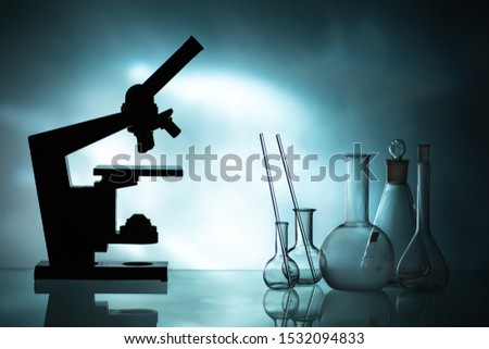 Test tubes. Beakers. Flasks. Beakers in the dark. A microscope next to the beakers. Sale of laboratory glassware. Science lab. Laboratory glassware and accessories. Test tubes in a medical center.