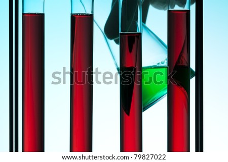 test tubes filled with red liquid, hand holding beaker with green liquid in background