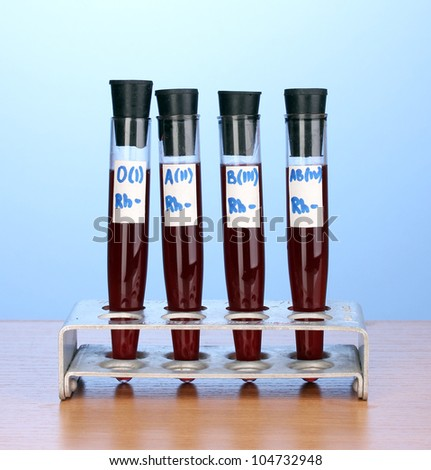 Test-tubes with blood on wooden table on blue background