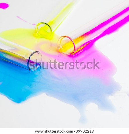 test tubes with colorful substances spilled on a white table in a lab - stock photo