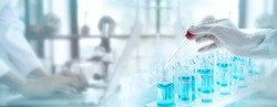 Test tubes with liquid in laboratory, Doctor hand holding dropper with dripping transparent glass pipette. scientist working with laptop background for banner size text space.