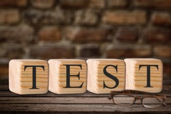 Test word made of wood block. Business concept. Education quality control.