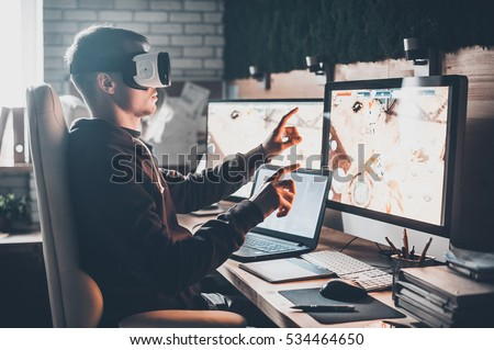 Testing games. Young man wearing virtual reality headset and gesturing while sitting at his desk in creative office