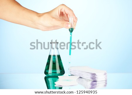 Testing sanitary pads for absorbency, on blue background close-up