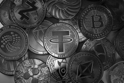 Tether USDT, Bitcoin and other altcoins cryptocurrency physical coins placed on top of each other and lit with selective lights.