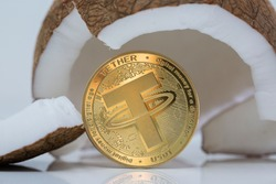 Tether USDT cryptocurrency physical coin placed next to broken coconut on the white reflective table. Macro shot.