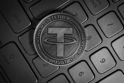Tether USDT Cryptocurrency physical coin placed on computer keyboard