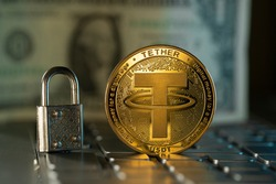Tether USDT cryptocurrency physical coin placed on computer keyboard and small lock next to it.