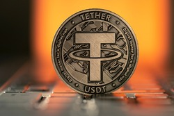 Tether USDT Cryptocurrency physical coin placed on laptop keyboard and lit with orange light from behind.