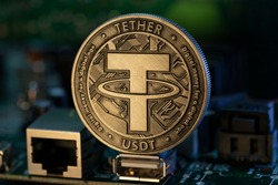 Tether USDT cryptocurrency physical coin placed on microscheme in the dark background. Selective focus.