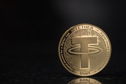 Tether USDT cryptocurrency physical coin placed on the reflective surface in the black background