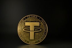 TETHER USDT cryptocurrency physical coin placed on the table in the dark background. Macro Shot.