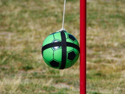 Tetherball Totem Ball attached to a red metal pole with grass in the background and space for graphics